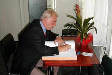 Dyrektor Dietmar Mayer dokonuje pamiątkowego wpisu do księgi gości Szpitala